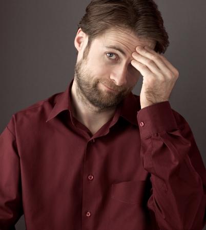 Veertig jaar oud schamen of verwarde man zijn hoofd krabben terwijl kijken naar de camera Close-up portret op een grijze achtergrond