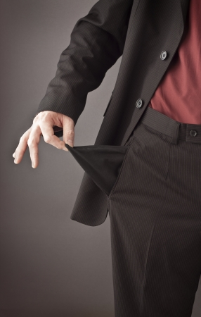 cheated: Poor businessman turning his empty pocket inside out to show his broke and out of money  Recession or financial crisis concept