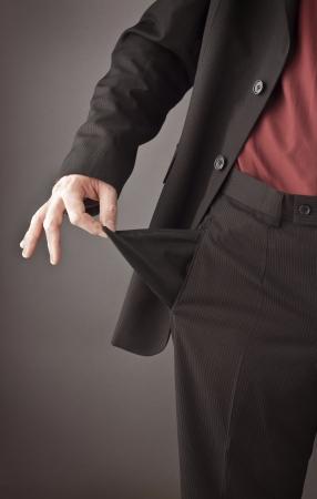 Slechte zakenman te draaien zijn lege zak binnenstebuiten om zijn brak en uit geld recessie of financiële crisis concept tonen