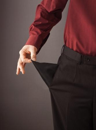Schlechte Geschäftsmann Drehen seine leere Tasche von innen nach außen zu seinem pleite und das Geld Rezession oder Finanzkrise Konzept zeigen
