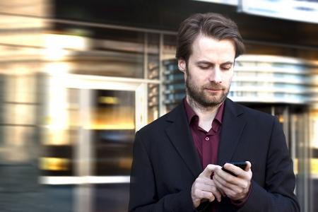 Vierzig Jahre alte Geschäftsmann stehend außerhalb modernes Bürogebäude suchen auf einem Mobiltelefon