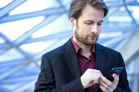 Vierzig Jahre alte Geschäftsmann standing in modernen Bürogebäude suchen auf einem Mobiltelefon