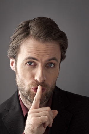 Portrait of forty years old businessman with finger on his lips trying to hide a secret or asking for silence