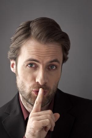 Portrait der 40 Jahre alte Geschäftsmann mit dem Finger auf seine Lippen versucht, ein Geheimnis zu verbergen oder fragen nach Stille
