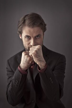 office force: Aggressive forty years old businessman in a boxing stance - unfair business competition or mafia concept Stock Photo