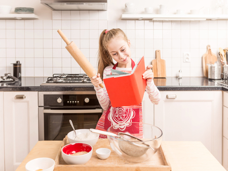 Happy smiling seven years old caucasian blond child girl looking for the recipe in the book. Kitchen - baking ingredients around. Stock fotó