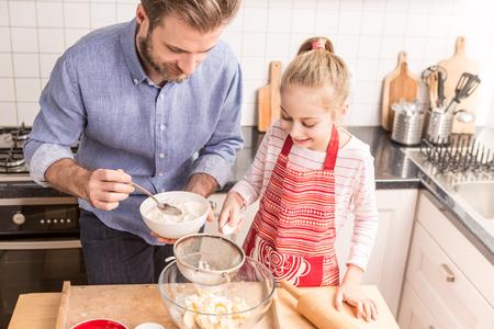 Lachend blanke vader en dochter voorbereiding koekjesdeeg in de keuken. Bakken - gelukkig gezin tijd.