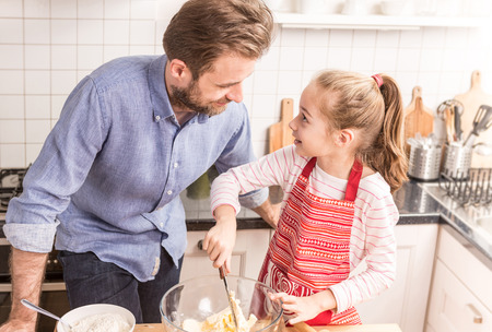 family time: Smiling caucasian father and daughter preparing cookie dough in the kitchen. Baking - happy family time. Stock Photo