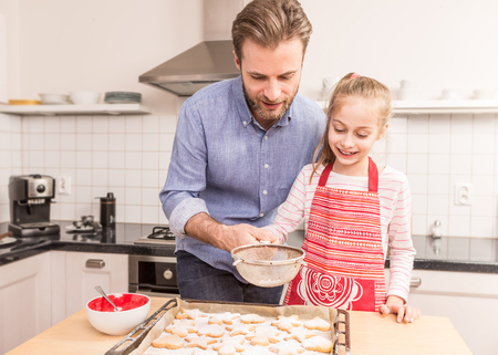 powdered sugar: Smiling caucasian father and daughter sprinkling powdered sugar on homemade cookies. Baking - happy family time in the kitchen.