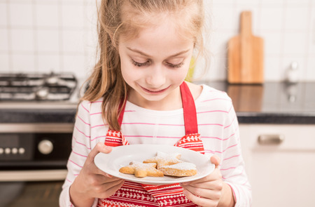 Happy smiling seven years old caucasian blond child girl looking at the freshly baked homemade cookies in the kitchen. 版權商用圖片