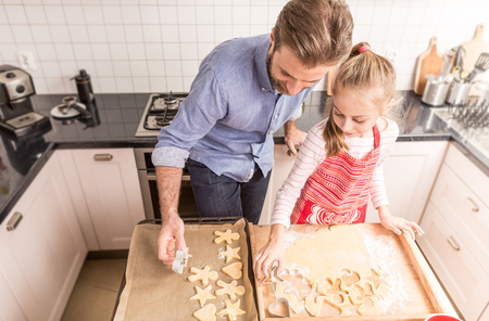 family time: Smiling caucasian father and daughter having fun while preparing cookies to bake. Kitchen - happy family time. Stock Photo