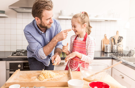 Smiling caucasian father and daughter having fun while preparing cookie dough in the kitchen. Baking - happy family time. Archivio Fotografico