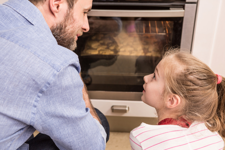 oven: Happy caucasian father and daughter waiting near the kitchen oven for the homemade cookies. Baking - happy family time. Stock Photo
