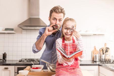 Kaukasischen Vater und Tochter, die Spaß während immer bereit, Plätzchen zu backen in der Küche - glückliche Familie Zeit. Lizenzfreie Bilder