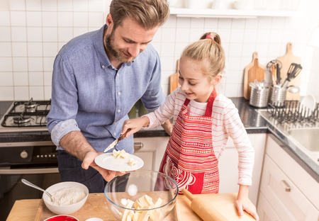 prepare: Smiling caucasian father and daughter preparing cookie dough in the kitchen. Baking - happy family time. Stock Photo