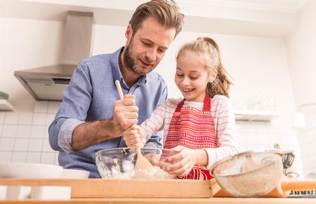 Caucásico sonriente padre e hija que preparan la masa para galletas en la cocina. Hornear - tiempo de la familia feliz.
