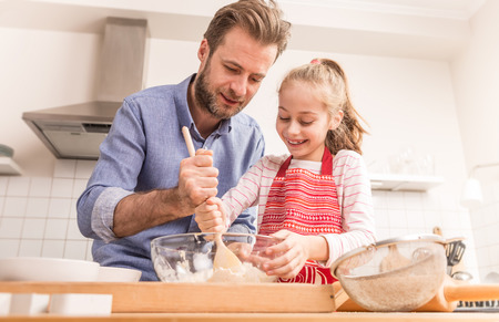 hobbies: Smiling caucasian father and daughter preparing cookie dough in the kitchen. Baking - happy family time. Stock Photo