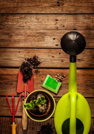 Tuingereedschap, gieter, zaden, planten en bodem op vintage houten tafel. Lente in de tuin concept achtergrond met vrije ruimte voor tekst.