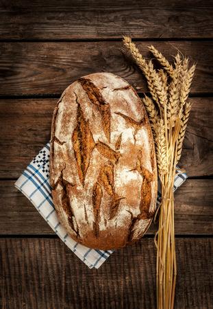Rustiek brood en tarwe op een oude vintage planked houten tafel. Donkere humeurige stilleven. Stockfoto
