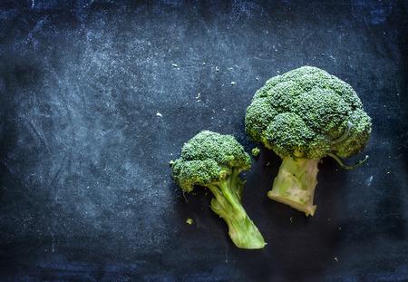 Rohem Broccoli auf schwarzem Tafel. Hintergrund mit Raum für freien Text. Lizenzfreie Bilder