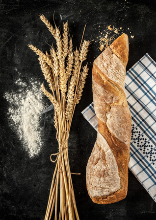 moody: Rustic bread roll or french baguette, wheat and flour on black chalkboard. Rural kitchen or bakery.