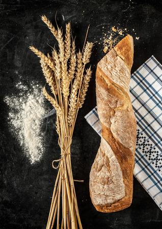 Rustiek broodje of Frans stokbrood, tarwe en bloem op zwart bord. Landelijke keuken of bakkerij.