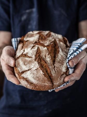 panadero: Panadero hombre que sostiene el pan orgánico rústico de pan en las manos - panadería rural. La luz natural, fondo cambiante con el espacio de texto libre buena para el cartel o portada. Foto de archivo