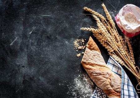 rollo rústico pan o baguette francés, el trigo y la harina en el pizarrón negro. cocina o panadería rural - fondo con el espacio de texto libre.