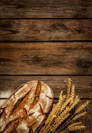 pain: Pain rustique et le bl� sur une vieille table en bois en planches vintage. Fond sombre morose avec espace libre de texte.