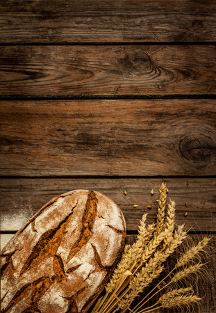 Rustic bread and wheat on an old vintage planked wood table. Dark moody background with free text space. Archivio Fotografico