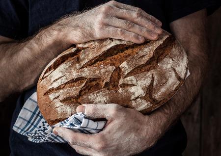 Baker man holding rustic organic loaf of bread in hands - rural bakery. Natural light, moody still life.