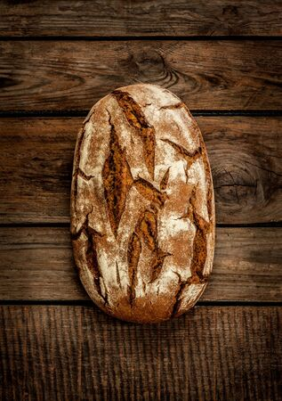 moody background: Rustic bread on an old vintage planked wood table. Dark moody background with free text space.