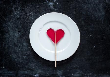 obesidad infantil: piruleta en forma de corazón rojo y placa blanca sobre fondo negro pizarra. San Valentín concepto de comida del día.