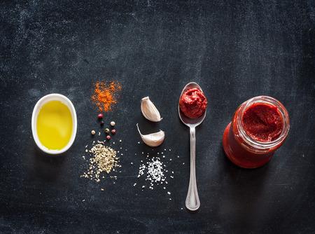 Pizza topping ingredienti per la salsa o ricetta su sfondo nero. Sfondo con spazio testo libero.