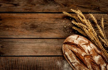 素朴なパンや小麦古いビンテージ板敷の木製テーブルの上。フリー テキスト スペースを持つ暗い不機嫌そうな背景。 写真素材