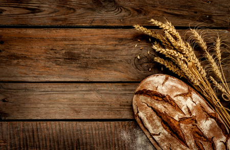 Rustic bread and wheat on an old vintage planked wood table. Dark moody background with free text space. Stock Photo