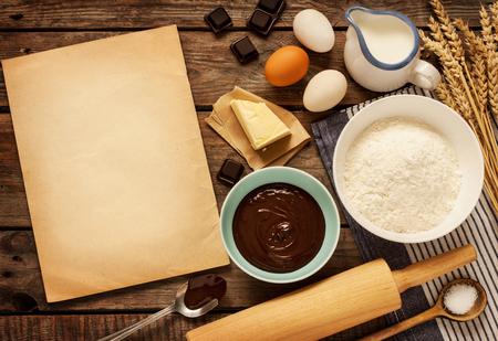 Landelijke vintage houten keukentafel met oude lege vel papier, bakken ingrediënten en kookgerei bakken.