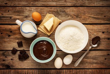 Baking chocolate cake in ländlichen oder rustikale Küche. Teig Rezept Zutaten (Eier, Mehl, Milch, Butter) auf Vintage-Holz-Tabelle von oben.
