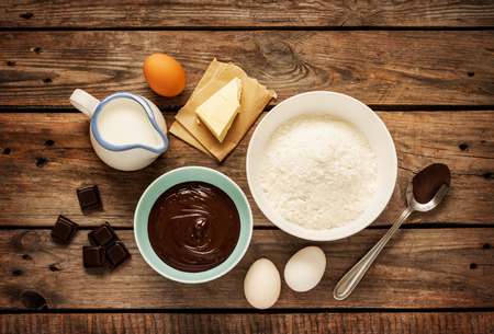Baking chocolate cake in rural or rustic kitchen. Dough recipe ingredients (eggs, flour, milk, butter) on vintage wood table from above. Stock Photo