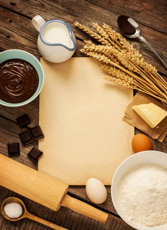 Rural vintage wooden kitchen table with old blank sheet of paper, baking cake ingredients (chocolate, eggs, flour, milk, butter, sugar) and cooking utensils around. Background layout with free recipe text space.