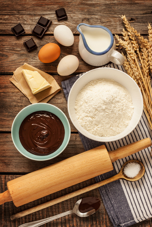 Baking chocolate cake in rural or rustic kitchen. Dough recipe ingredients (eggs, flour, milk, butter, sugar) on vintage wood table from above. Archivio Fotografico