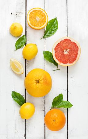 Las frutas cítricas (limón, pomelo y naranja) con hojas frescas húmedas en la mesa de madera blanca de la vendimia - todavía vida desde arriba