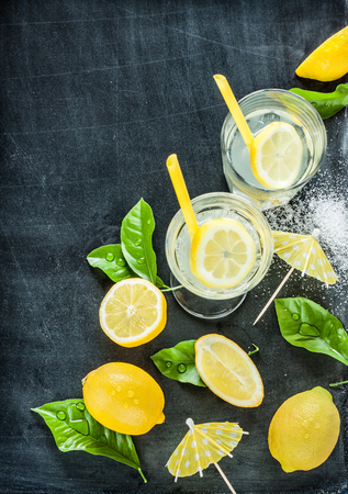Lemonade with lemons and fresh wet leaves on black chalkboard from above. Background layout with free text space.