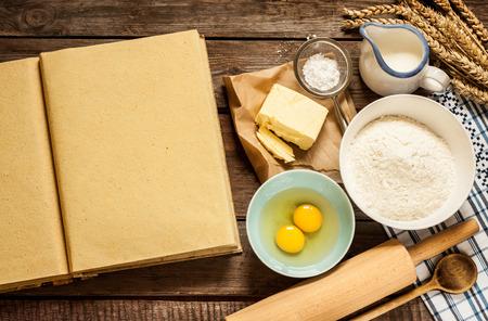Landelijk vintage houten keukentafel met lege kookboek, bakken cake ingrediënten (eieren, bloem, melk, boter, suiker) en kookgerei rond.