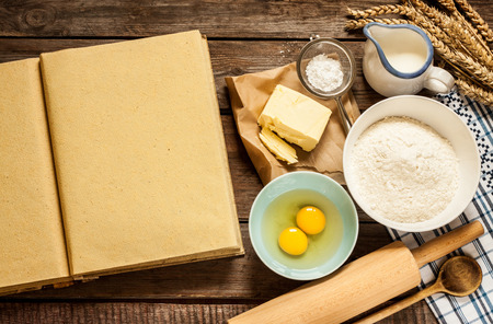 sugar: Rural vintage wood kitchen table with blank cook book, baking cake ingredients (eggs, flour, milk, butter, sugar) and cooking utensils around. Stock Photo