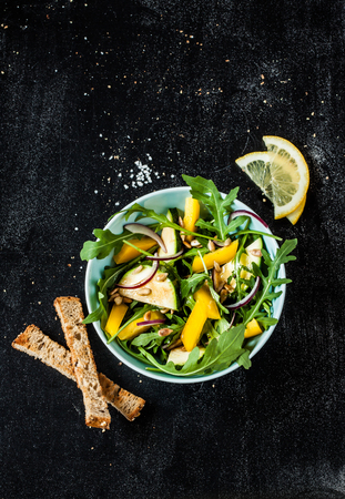 spring green: Fresh green spring salad with arugula (rucola), yellow pepper, zucchini, sunflower seeds and croutons on black chalkboard background from above. Stock Photo