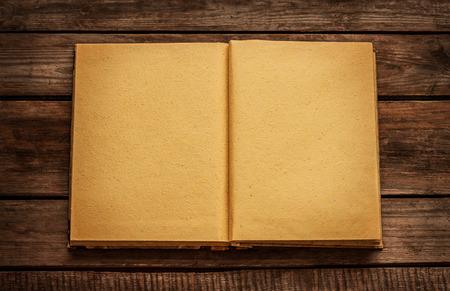 Oude lege open boek op vintage planked houten tafel van boven - rustieke achtergrond met tekstruimte