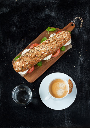 Sandwich (mozzarella cheese, tomatoes and fresh basil), coffee and water on black chalkboard background. Cafe table from above.