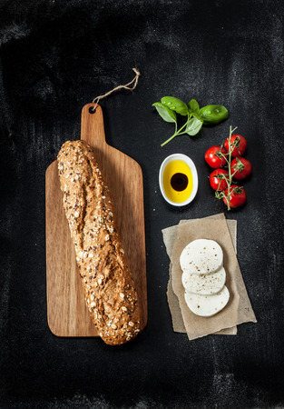 Sandwich recipe - bread roll, mozzarella cheese, cherry tomatoes and basil. Ingredients on black chalkboard from above. Stock fotó