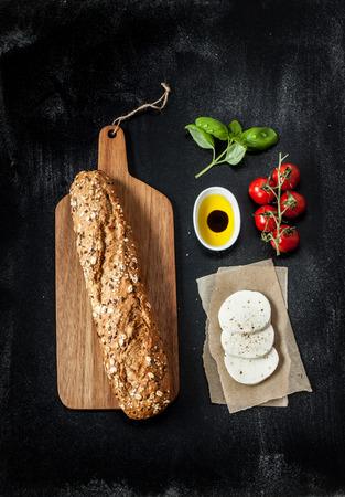 Sandwich Rezept - Brötchen, Mozzarella-Käse, Tomaten und Basilikum. Zutaten auf schwarze Tafel von oben. Lizenzfreie Bilder